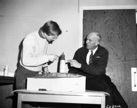 Kal Hinrikus showing model of lighthouse to Captain Mel Tanner