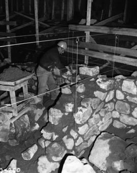 Stone masons constructing foundation for Chateau St. Louisbourg, facing South